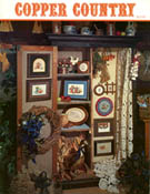 Cover photo of Stoney Creek Book 2 Copper Country cross stitch pieces displayed in a country cupboard